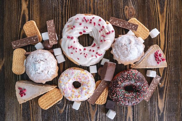 Alimentos doces prejudiciais em um fundo escuro de madeira
