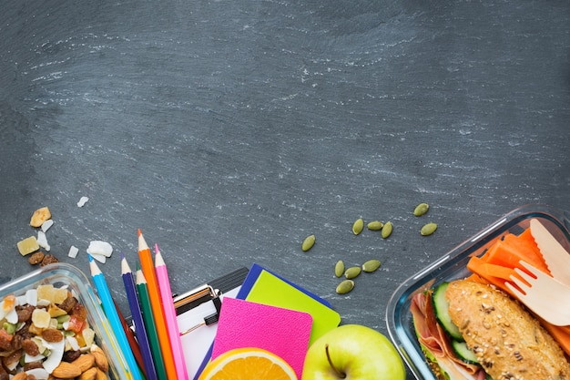 Alimentos e bebidas, natureza morta, dieta e nutrição, alimentação saudável, conceito de take away. caixa de merenda escolar e artigos de papelaria. vista superior plana, copie o fundo do quadro-negro