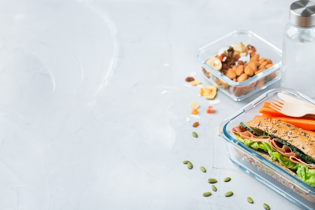 Alimentos e bebidas, natureza morta, dieta e nutrição, alimentação saudável, conceito de take away. lancheira com sanduíche, frutas, vegetais, mistura de nozes e garrafa de água. copie o fundo do espaço