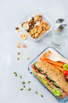 Alimentos e bebidas, natureza morta, dieta e nutrição, alimentação saudável, conceito de take away. lancheira com sanduíche, frutas, vegetais, mistura de nozes e garrafa de água. vista superior do plano de fundo