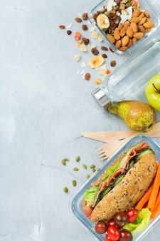 Alimentos e bebidas, natureza morta, dieta e nutrição, alimentação saudável, conceito de take away. lancheira com sanduíche, frutas, vegetais, mistura de nozes e garrafa de água. vista superior plana, copie o fundo do espaço