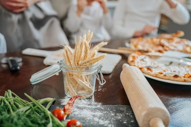 Alimentos e vegetais ogrânicos e saudáveis. rolo da massa com farinha na mesa da cozinha moderna durante o dia.