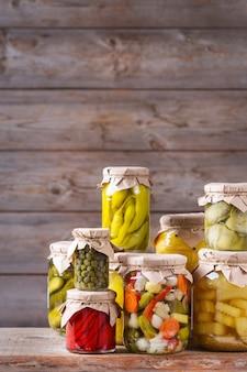 Alimentos em conserva e fermentados. variedade de potes caseiros com uma variedade de vegetais em conserva e marinados em uma mesa de madeira. limpeza, economia doméstica, preservação da colheita