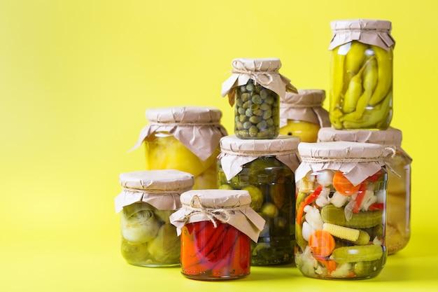 Alimentos em conserva e fermentados. variedade de potes caseiros com uma variedade de vegetais em conserva e marinados em uma mesa. limpeza, economia doméstica, preservação da colheita