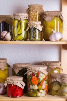 Alimentos em conserva e fermentados. variedade de potes caseiros com uma variedade de vegetais em conserva e marinados em uma prateleira no depósito. limpeza, economia doméstica, preservação da colheita