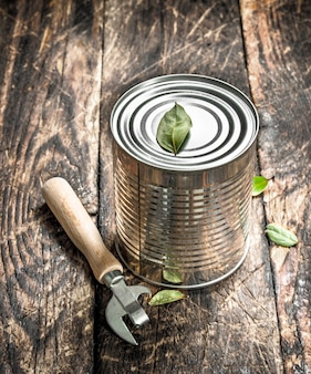 Alimentos em lata com abridor. sobre um fundo de madeira.