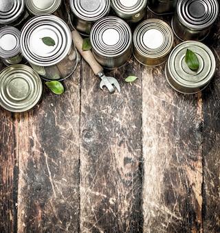 Alimentos em latas com abridor. sobre um fundo de madeira.