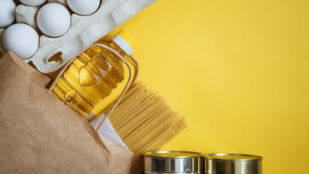 Alimentos em uma caixa de papelão em um fundo amarelo