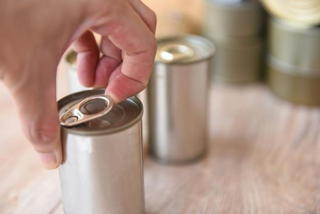 Alimentos enlatados abertos de mão em lata de metal no fundo de madeira