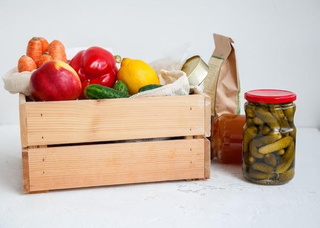 Alimentos enlatados, cereais, frutas, vegetais diferentes em um branco.