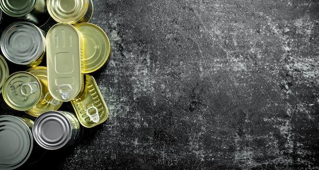 Alimentos enlatados em latas fechadas. em fundo escuro rústico