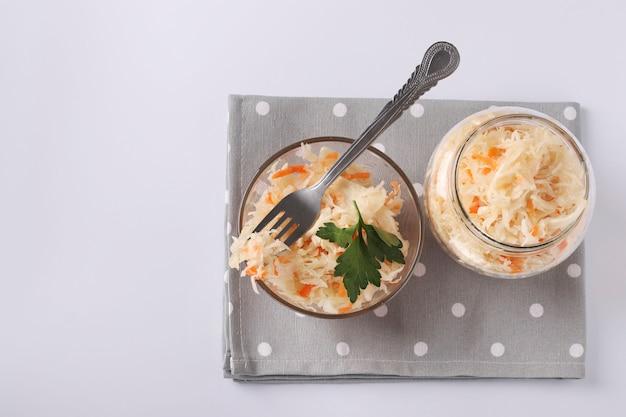 Alimentos fermentados, chucrute caseiro com cenouras em uma tigela e frasco em fundo branco, vista superior, espaço de cópia