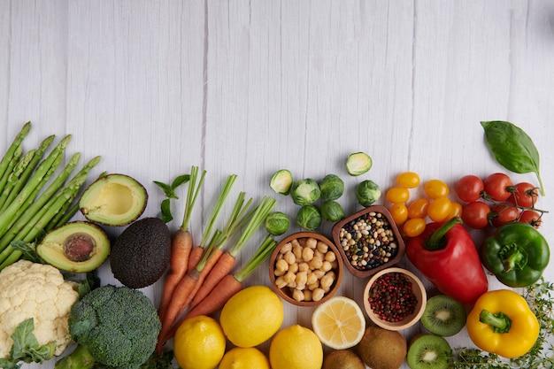 Alimentos fotografia diferentes frutas e vegetais na superfície da mesa de madeira branca.