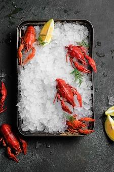 Alimentos frescos de lagostim em um fundo de placa preta. lanche de lagostins vermelhos com ervas especiarias, limão, alecrim e gelo em restaurante gourmet comida saudável