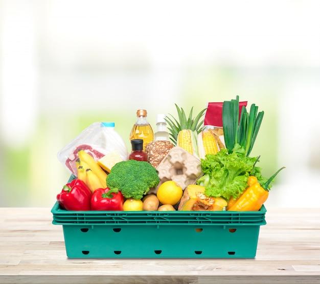 Alimentos frescos e mantimentos na caixa de bandeja na bancada da cozinha