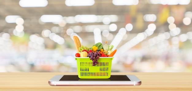 Alimentos frescos e vegetais na cesta de compras no smartphone móvel na mesa de madeira