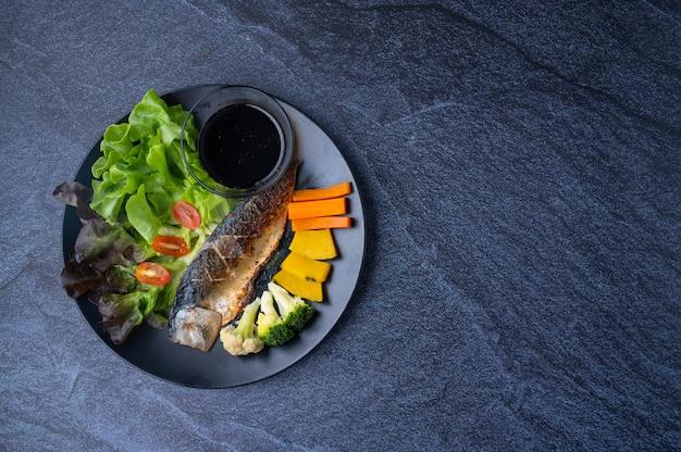 Alimentos limpos e saudáveis que consistem em peixe saba grelhado, ervas vegetais e molhos japoneses