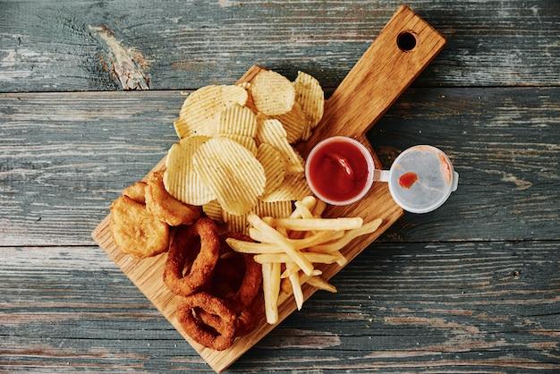 Alimentos não saudáveis e lixo. diferentes tipos de fastfood e lanches na mesa