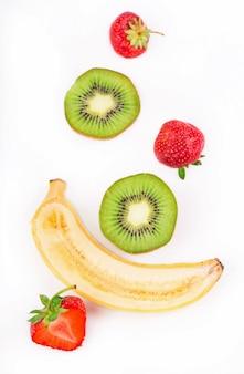 Alimentos orgânicos, alimentos saudáveis, kiwi, morango e bananakiwi, morango e banana em uma superfície branca