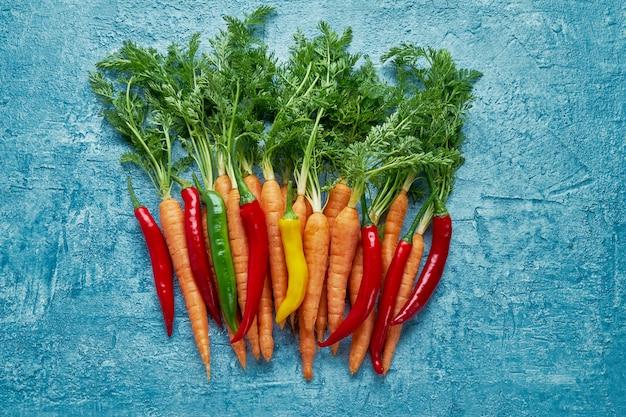 Alimentos orgânicos cenouras vermelhas e pimenta colorida em fundo azul brilhante