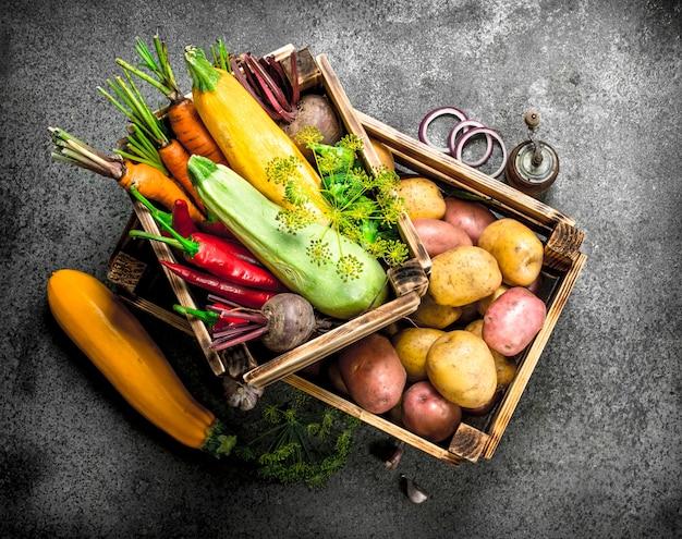 Alimentos orgânicos colheita fresca de vegetais em uma caixa velha em um fundo rústico