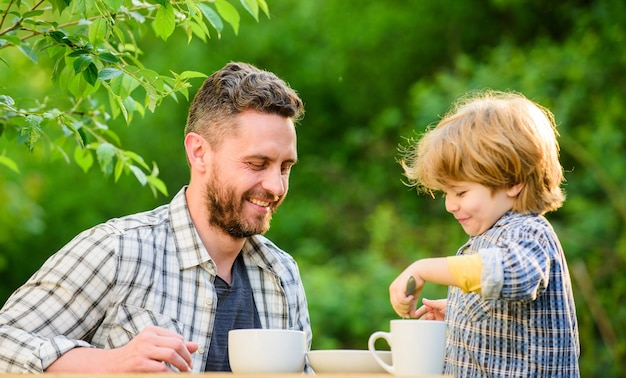 Alimentos orgânicos e naturais. menino pequeno com o pai. comida saudável. ligação do dia da família. pai e filho comem ao ar livre. eles adoram comer juntos. café da manhã de fim de semana. dia da família. tradições familiares.