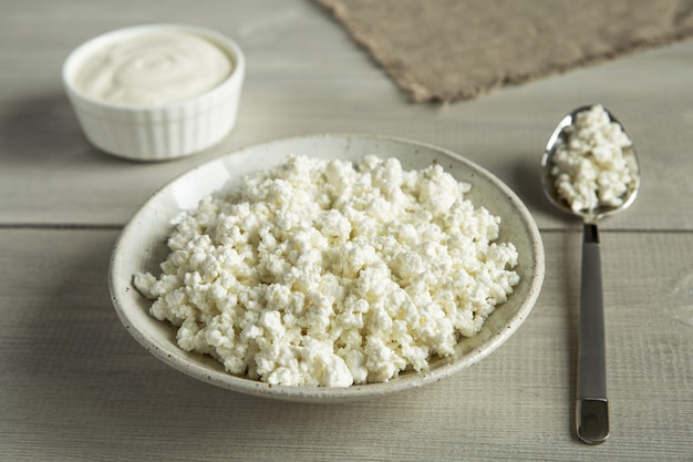 Alimentos orgânicos, produtos lácteos, queijo cottage creme azedo em utensílios brancos sobre fundo de madeira close-up
