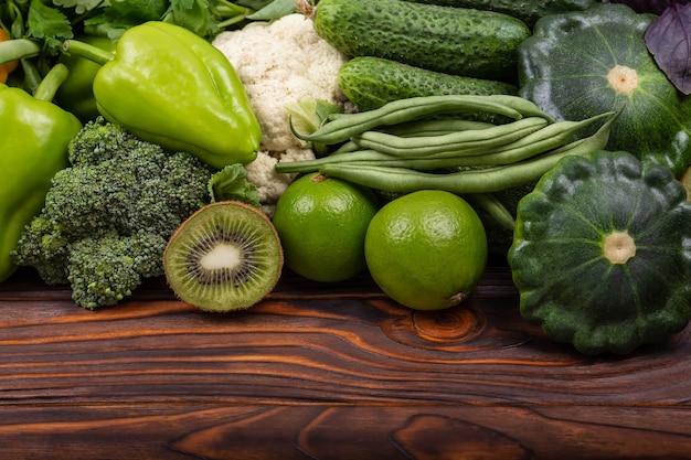 Alimentos orgânicos saudáveis vegetais verdes e ervas em fundo de madeira