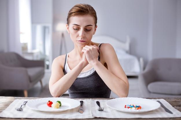 Alimentos ou remédios. mulher triste com fome sentada em frente aos pratos enquanto faz uma escolha