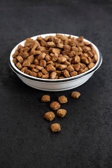 Alimentos para animais de estimação secos em uma tigela de cerâmica branca sobre fundo preto, com espaço de cópia