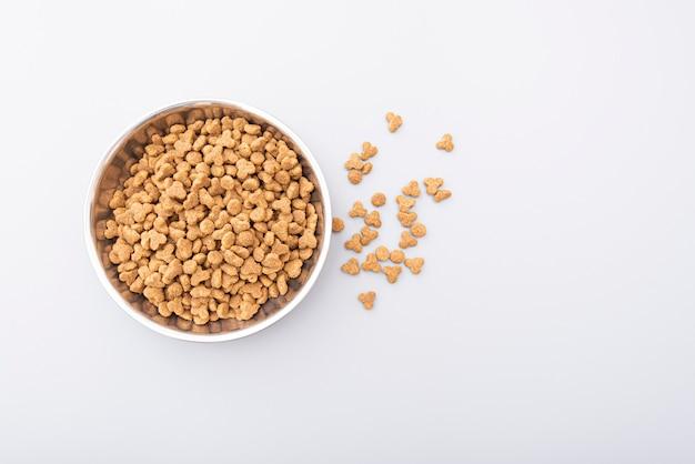 Alimentos para animais em tigela de ferro na superfície cinza