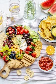 Alimentos para piquenique de verão com tábua de queijos e frutas