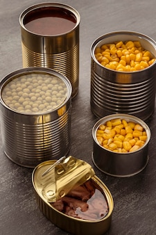Alimentos preservados de alto ângulo em latas altas redondas