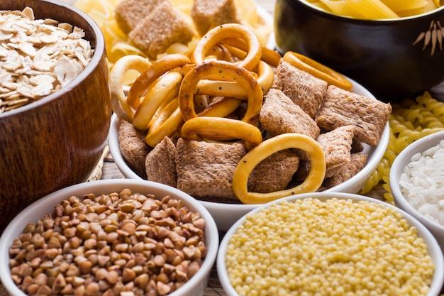 Alimentos ricos em carboidratos na mesa de madeira rústica.