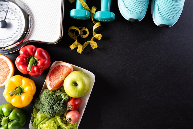 Alimentos saudáveis com equipamentos de ginástica na parede preta.