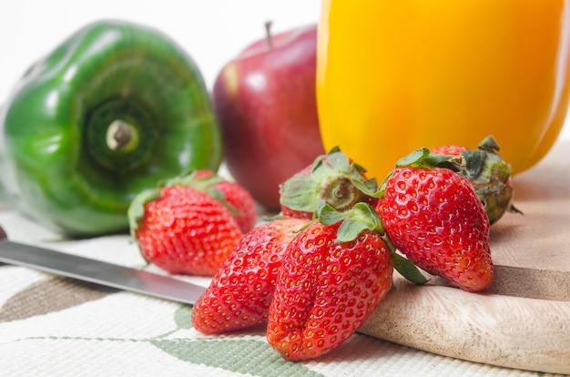 Alimentos saudáveis com frutas e legumes estão no bloco de desbastamento na cozinha