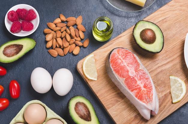 Alimentos saudáveis de baixo teor de carboidratos em fundo preto. conceito de dieta ceto