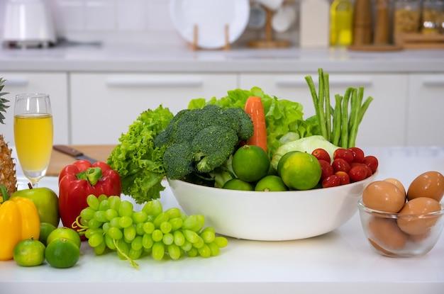 Alimentos saudáveis de vegetais frescos, frutas, ovos e suco de abacaxi na mesa branca da cozinha de casa