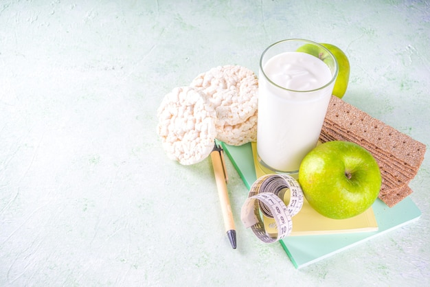 Alimentos saudáveis e conceito de perda de peso. maçã, iogurte, pão crocante de cereal saudável, caderno e fita métrica na parede verde-clara copie o espaço para texto