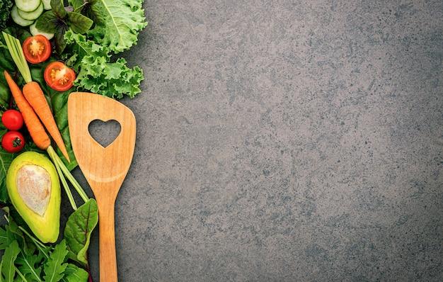 Alimentos saudáveis e cozinha conceito espátula de madeira e vegetais na pedra escura.