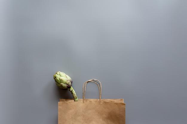 Alimentos saudáveis e orgânicos flay leigos conceito em fundo cinza. saco ecológico com alcachofra.