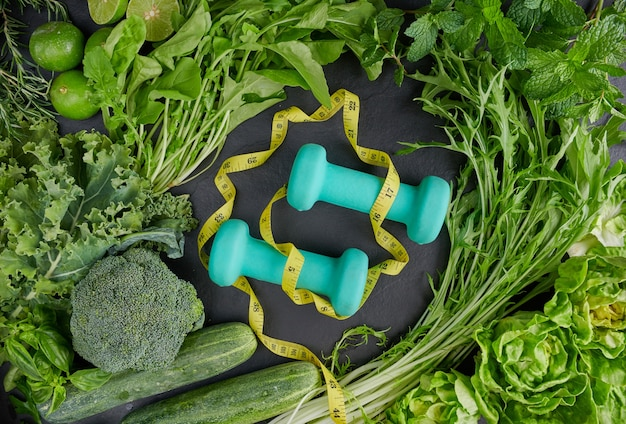 Alimentos saudáveis, halteres e fitas métricas