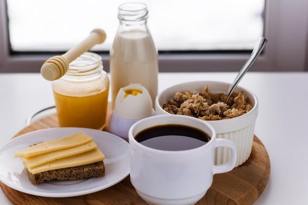 Alimentos saudáveis para o café da manhã, leite, mel, cereais, café, ovos cozidos, café, sanduíche com queijo