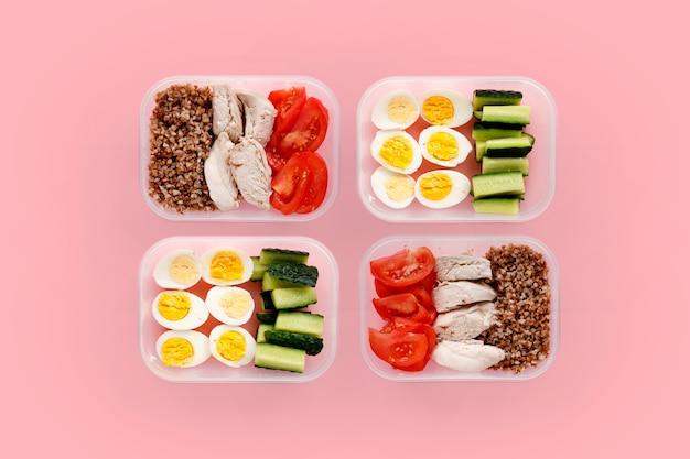Alimentos saudáveis para o dia todo. várias porções em recipientes em fundo rosa