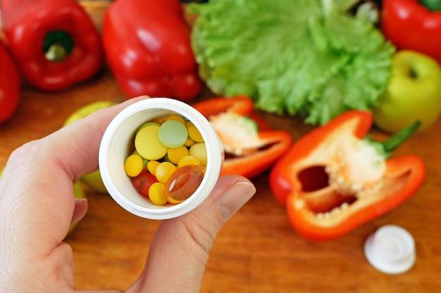 Alimentos saudáveis (vegetais, frutas) vs conceito de pílulas, closeup