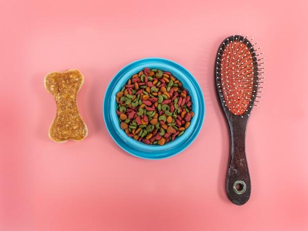Alimentos secos em tigelas com osso e pente para animais de estimação em fundo de cor. conceito de flat lay