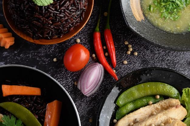 Alimentos variados e pratos de legumes, carne e peixe em uma mesa de pedra preta. vista do topo.