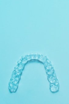 Alinhadores de dentes de colchetes dentais invisíveis em fundo turquesa. aparelhos plásticos, retentores odontológicos para endireitar os dentes.