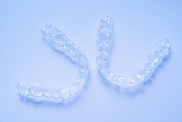 Alinhadores de dentes de colchetes dentais invisíveis sobre fundo azul. aparelhos plásticos, retentores odontológicos para endireitar os dentes.