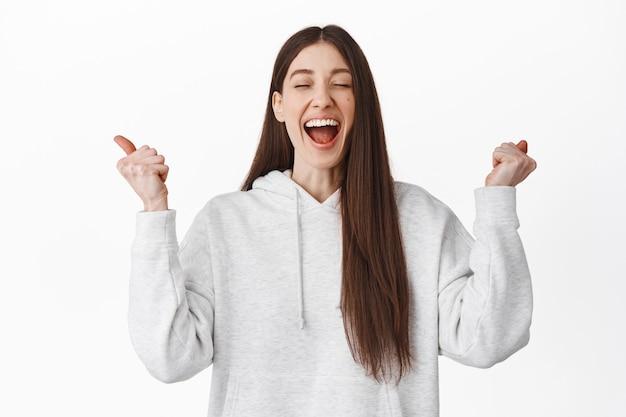Aliviada e feliz garota grita de empolgação e alegria, apertando as mãos com os olhos fechados e rindo, vencendo, atingir a meta, comemorar o sucesso e vencer, de pé sobre a parede branca
